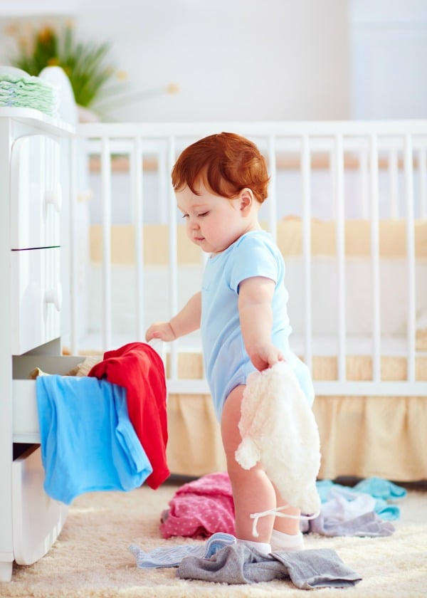 Young toddler pulling clothes out of dresser drawer.