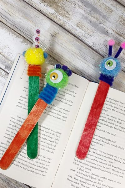 Finished yellow, green, and blue monster craft stick bookmarks laying on a book.