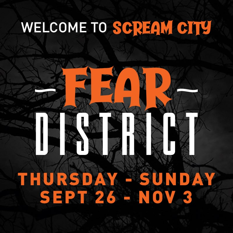 Orange and white text with dates for Fear District event with a dark background with a silhouette of tree branches