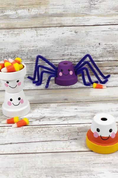 4 mini flower pots decorated to look like two ghosts, a spider, and a candy corn. Ghost pots stacked on top of each other with top one filled with candy corn.