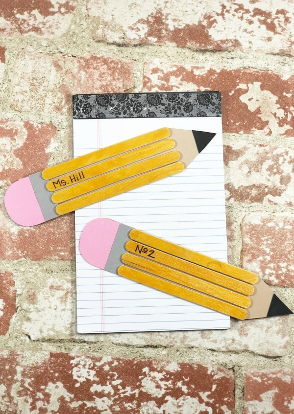 Two school pencils made with paper and wooden craft sticks on notebook with brick background