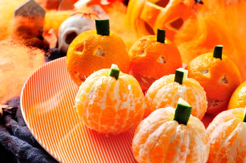 Tangerines decorated like pumpkins on orange plate