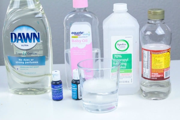 Bottle of dish soap, baby oil, corn syrup, water, and blue food dye on table for making ocean zone layer project