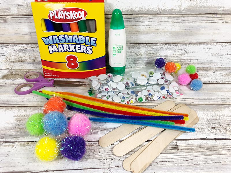 Box of markers, glue, googly eyes, assorted pom poms, craft sticks, and chenille stems laying on white board background.