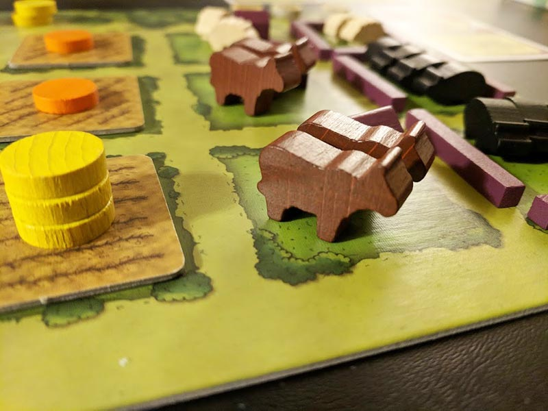 Close up of Agricola game board with fields and animal meeples.