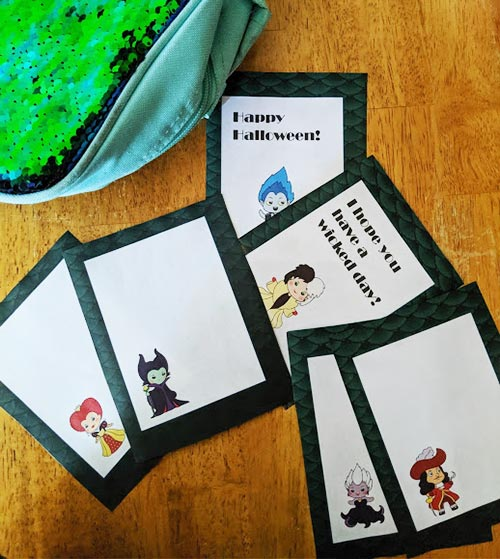 Printed Disney Villain lunch note cards cut apart and spread out on wood table with green and blue lunch box nearby.