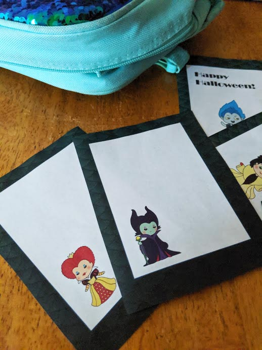 Blank lunch box notes with Queen of Hearts and Maleficent printed out and laying on table by lunchbox.