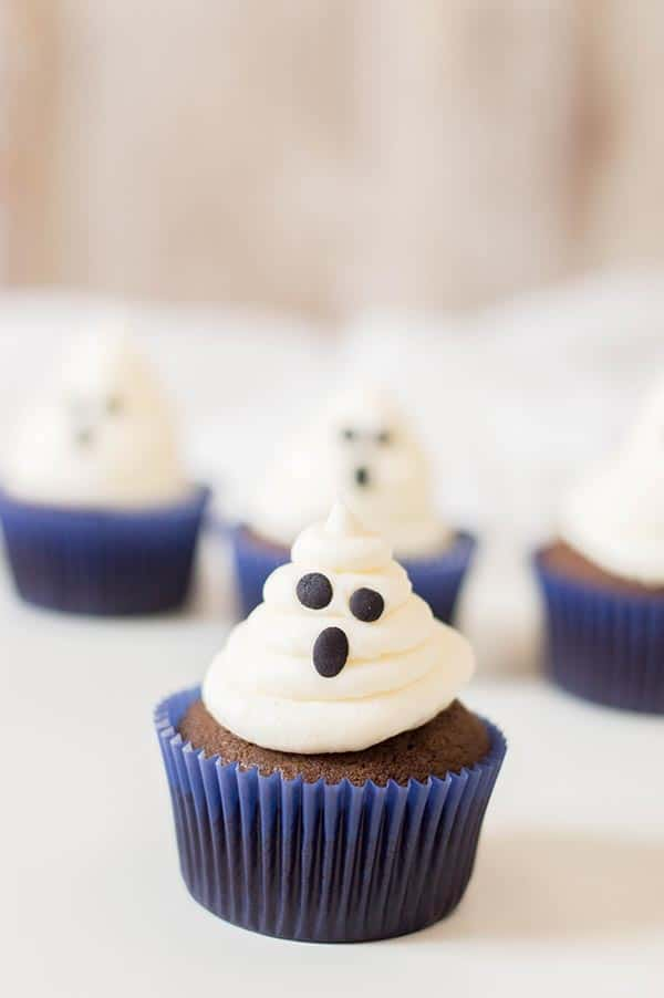 Chocolate cupcake in blue wrapper with marshmallow frosting ghost face. Cupcakes sitting on a white tablecloth