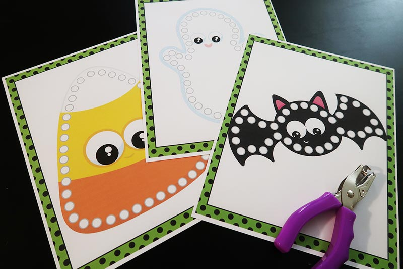Candy corn, ghost, and bat lacing cards printed on cardstock paper and laying on table next to hole puncher.