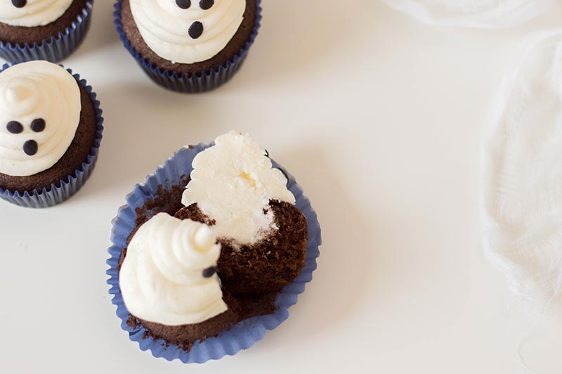 Completed chocolate marshmallow ghost cupcakes and one split open on a white background.