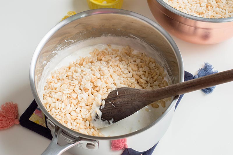 Mixing rice krispie cereal into melted butter and marshmallow mixture in silver saucepan
