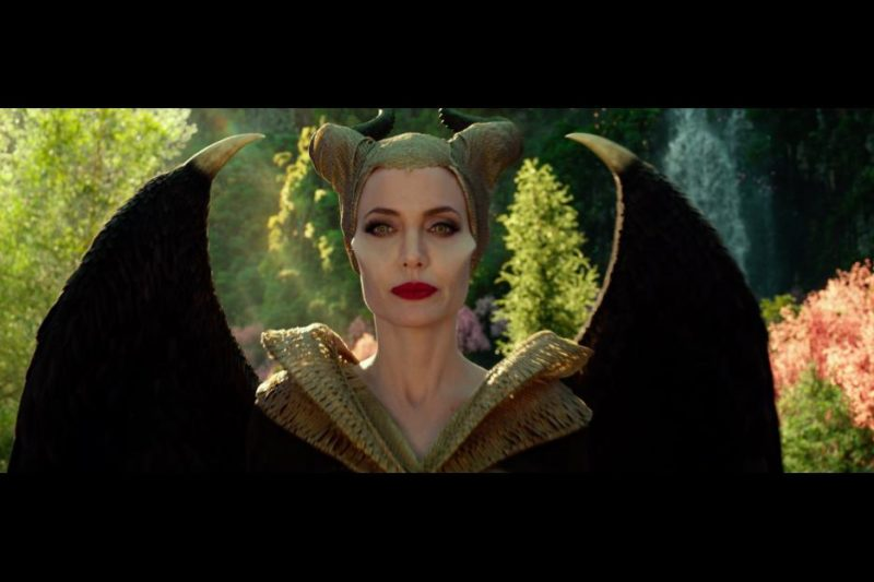 Maleficent standing, wearing tan robes and tan wrapped horns.