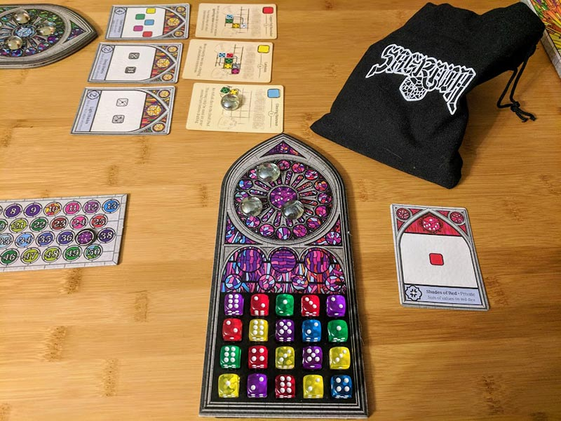 Sagrada dice game set up on table. Board is filled with dice.