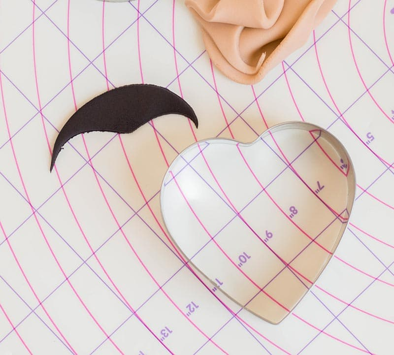 Demonstrating how to use heart cookie cutter to create hair with widows peak for fondant face