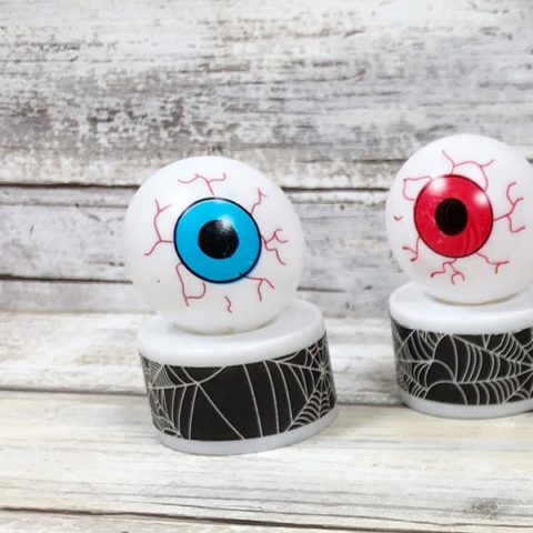 Two finished monster eyeball tea light crafts. One with blue iris and one with red iris.