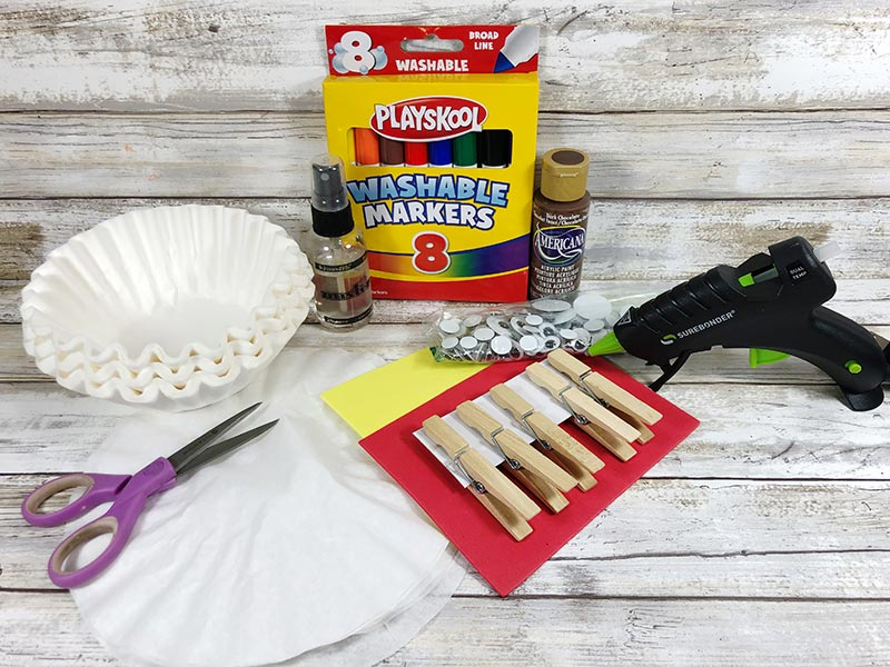 Coffee filters, clothespins, googly eyes, markers, and other craft supplies on white wood background.
