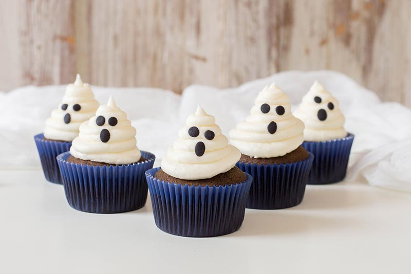 5 completed chocolate ghost cupcakes on white tabletop.