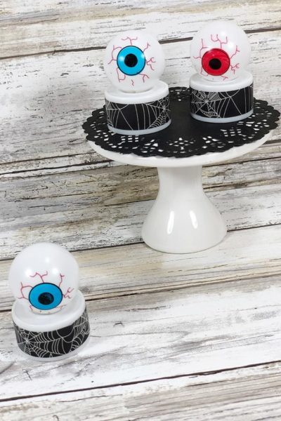 Two completed eyeball tea lights on white cake pedestal with black doily. One blue eyeball light on table next to pedestal