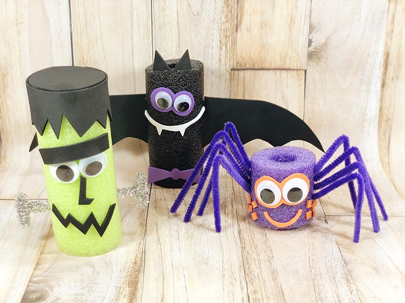 Frankenstein monster, bat, and spider pool noodle crafts standing on a light board background.