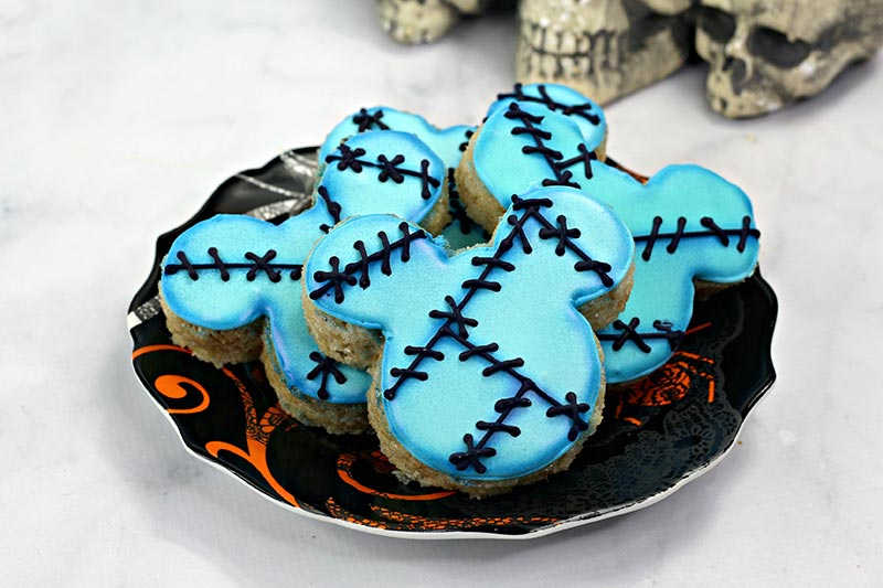 Mickey shaped rice crispy treats decorated with blue icing and black stitch marks. Several arranged on a Halloween plate.