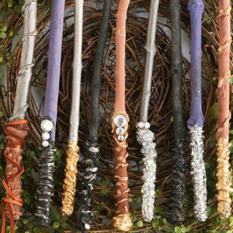 Set of six completed stick wands laying on wreath of greenery.