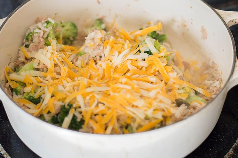 Shredded cheese on top of tuna and rice cooking in white pot