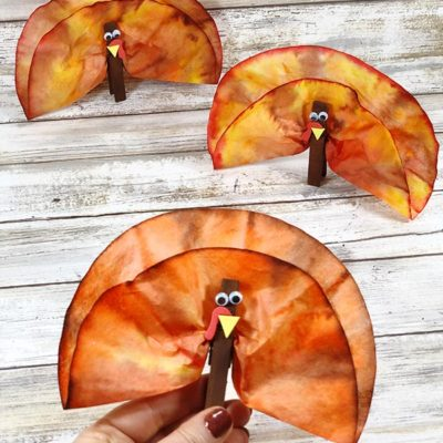 Three completed coffee filter turkey craft projects. Woman's hand holding one turkey. Two turkeys standing on white wood background.