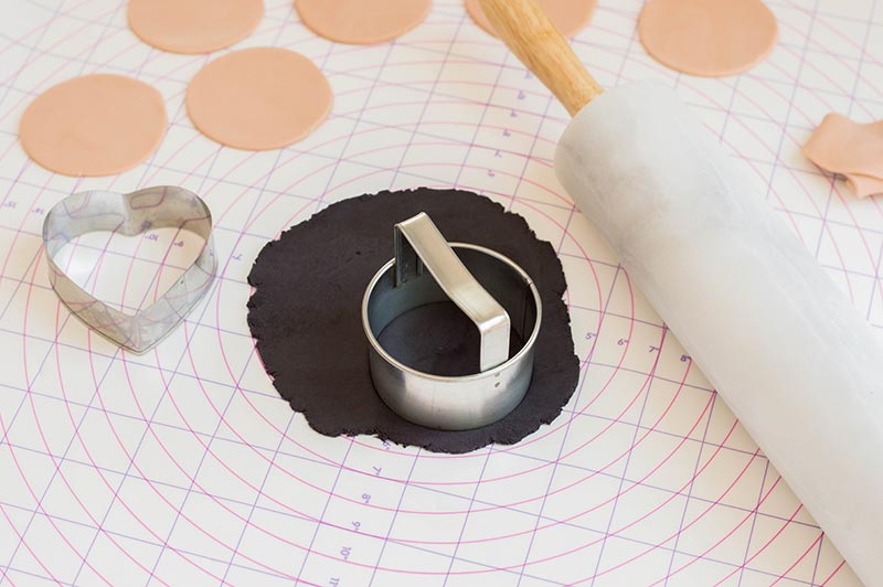 Circle cookie cutter cutting out beige and black fondant circles on pastry mat.
