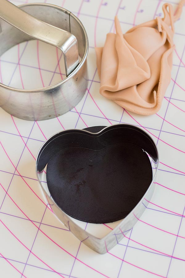 Heart shaped cookie cutter on black fondant. Circle cookie cutter and beige fondant scraps on pastry mat.