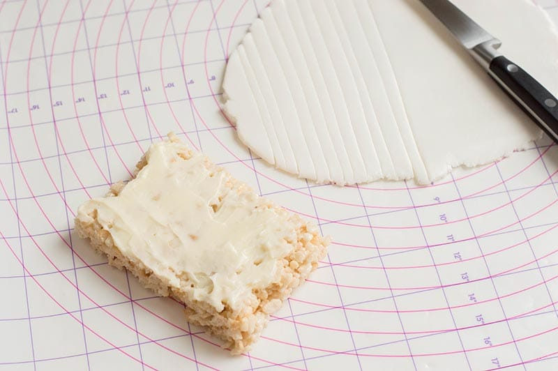 Frosted rice crispy treat on pastry mat next to rolled out white fondant.