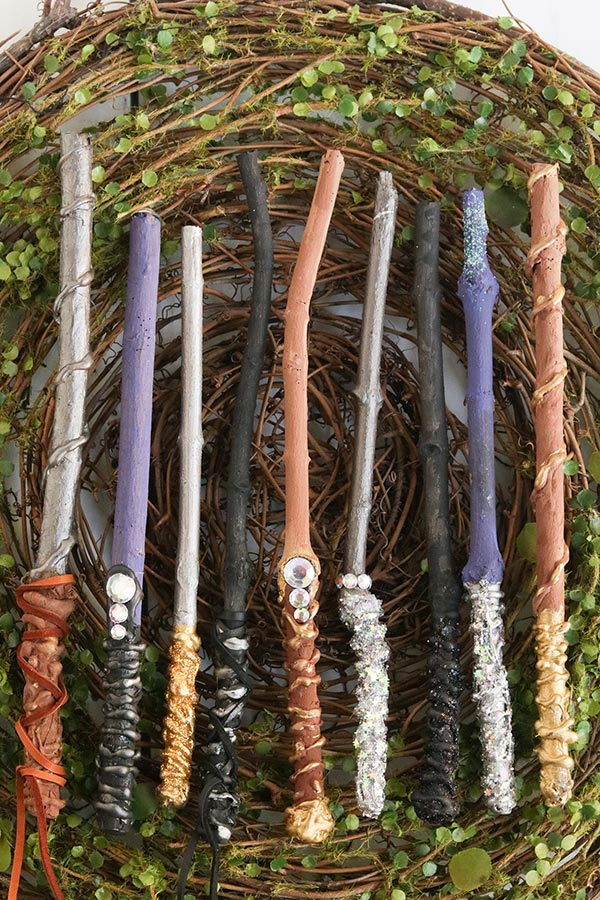 Completed set of homemade wands laying on a greenery.