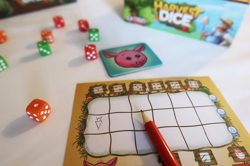 Harvest Dice game components on white table.