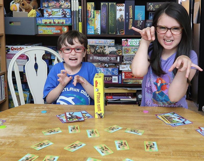 Author's son and daughter pretending to be dinosaurs while playing Dino World board game.