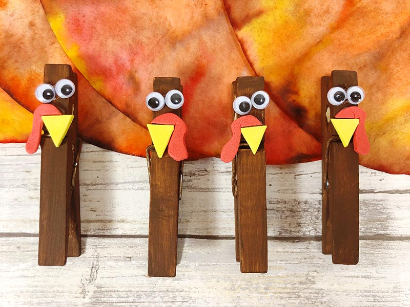 Close up of four clothespins decorated to look like turkeys.