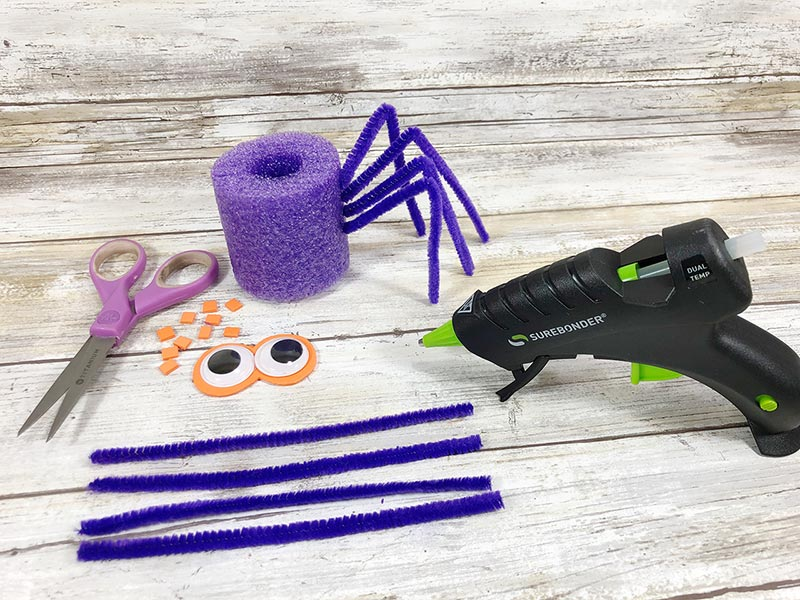 Supplies for pool noodle spider on light wood background. Half of pipe cleaners inserted in pool noodle for spider legs.