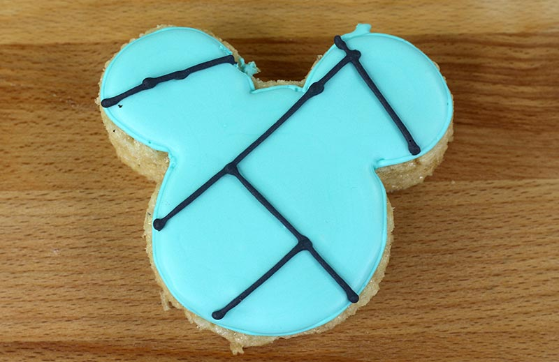 Rice crispy shaped like Mickey with teal icing on top and black lines to show how to make stitch marks for decoration.
