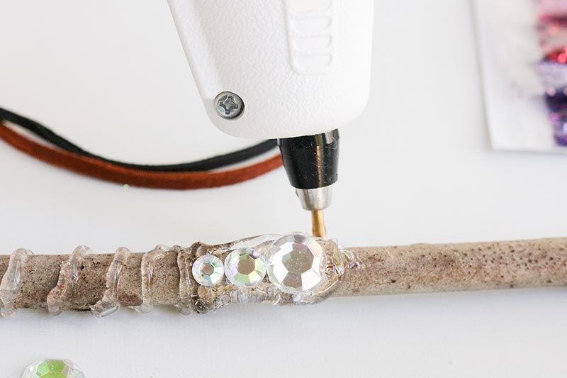 Close up of using hot glue gun to create wand handle and attach craft gems to the stick.