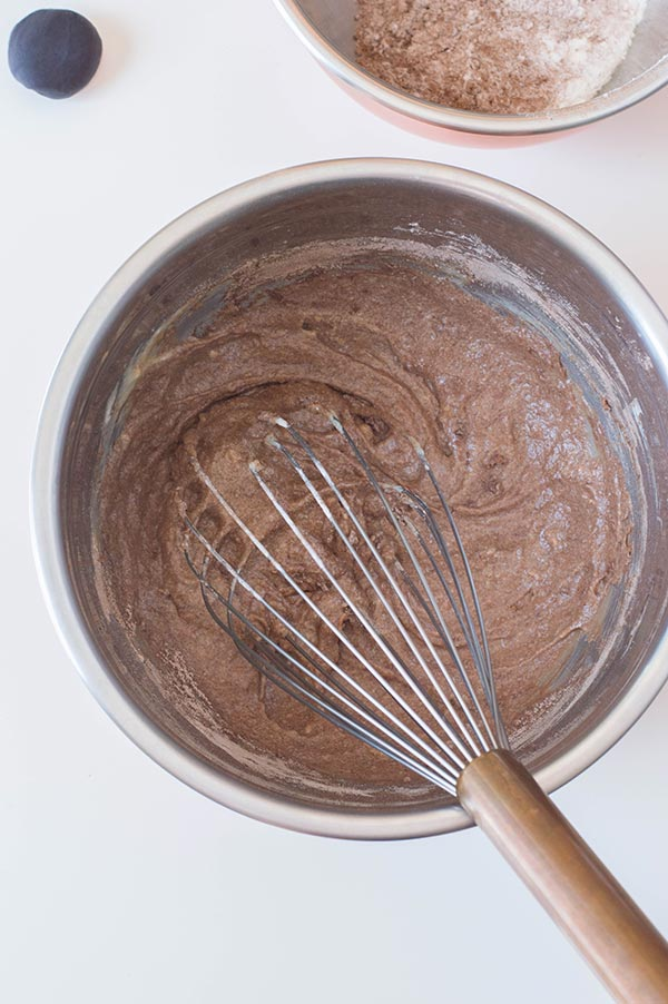Whisking dry ingredients to chocolate cupcake batter in silver mixing bowl.