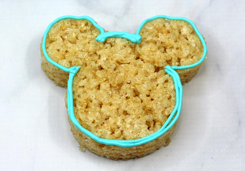 Mickey Mouse shaped rice crispy treat with blue icing outline.