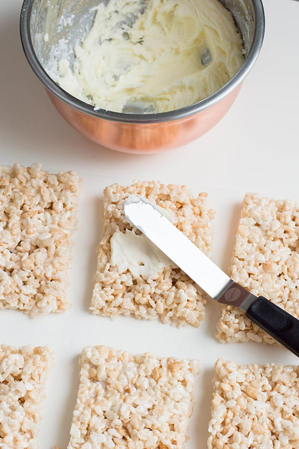Spreading buttercream icing on rice crispy treats with offset spatula.