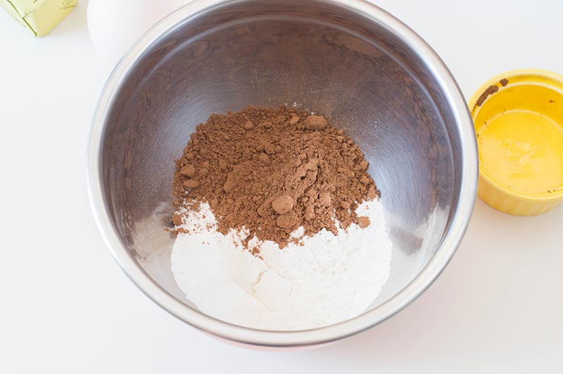Flour, coca powder, and other dry ingredients in a silver mixing bowl