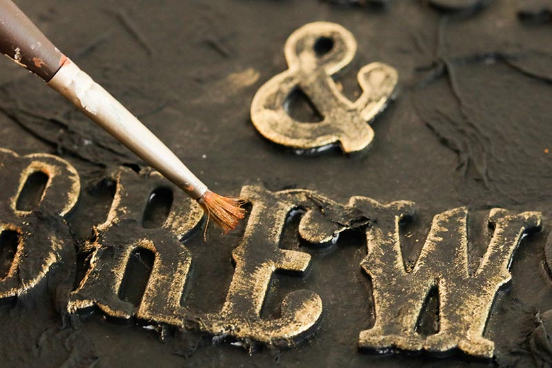 Close up of paint brush painting letters gold for diy spell book