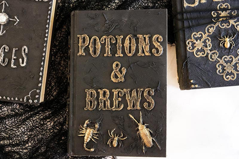 Completed spell books Halloween craft. 3 books laying on black gauze like fabric.