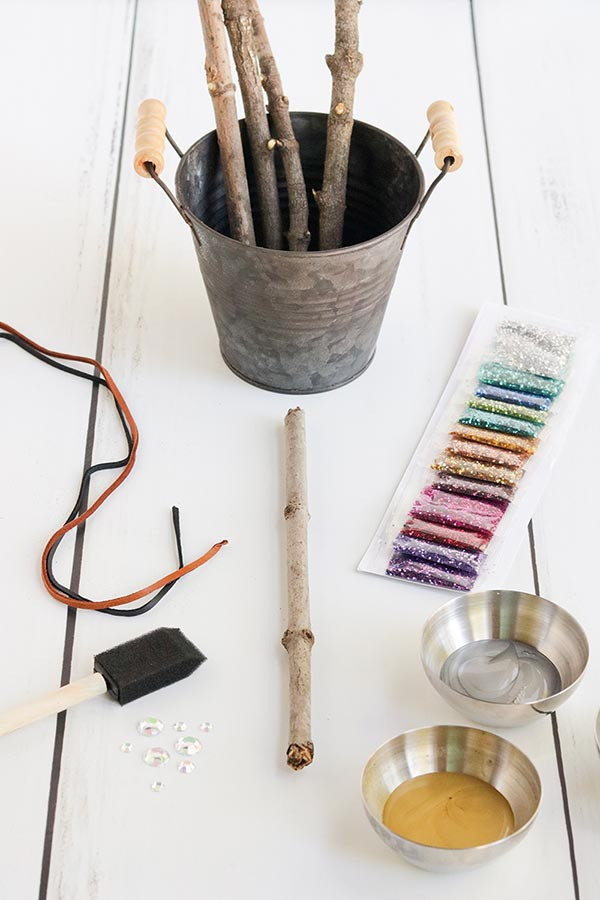 Sticks in a silver bucket and other supplies for wand craft on a white table.