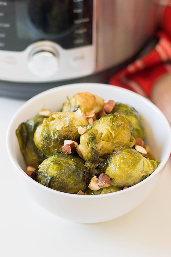 Brussels sprouts in small white bowl in front of pressure cooker.