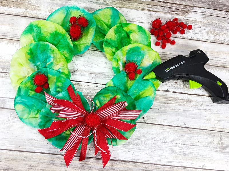 Hot gluing red pom poms onto coffee filter wreath.