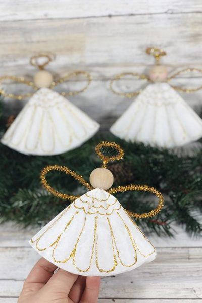 Hand holding one completed coffee filter angel ornament and two more angels sitting on evergreen sprig.