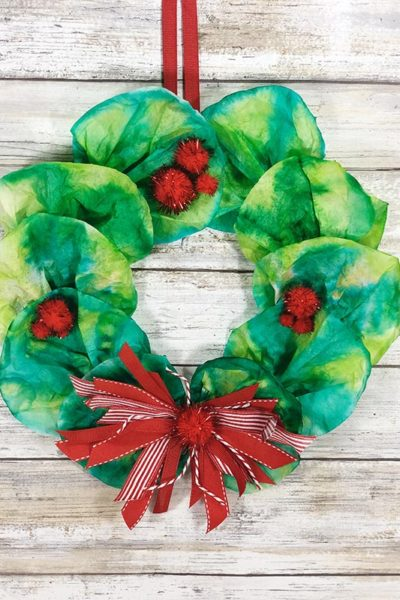 Christmas wreath made with coffee filters hanging in front of white wood backdrop.