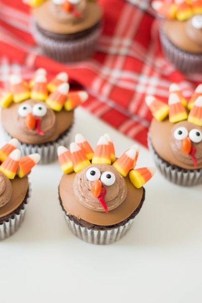 Cupcakes decorated like turkeys on white counter and red plaid cloth.