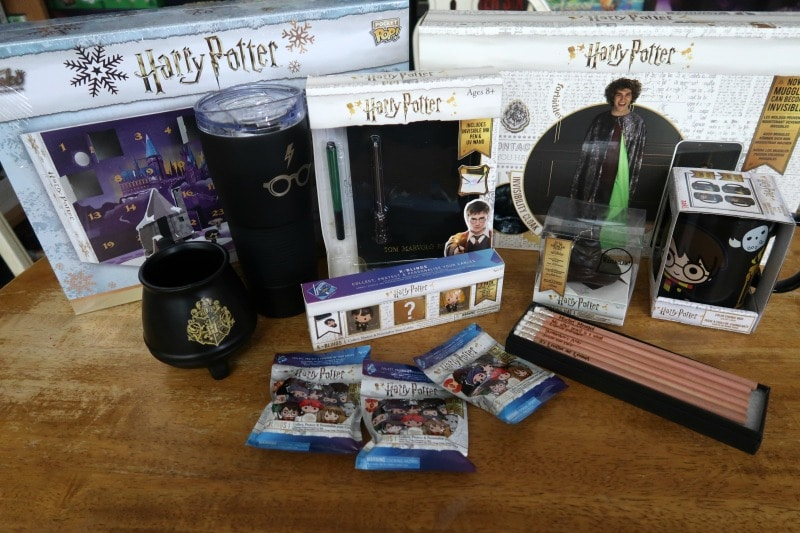 Harry Potter advent calendar, mugs, tumbler, pencils, invisibility cloak, diary, keychain, and kblings arranged on top of table.